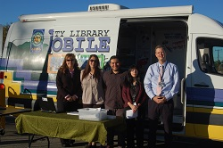 Employees by the Bookmobile for the Kid Card Kickoff event